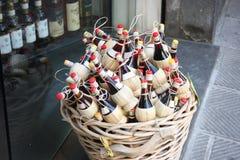 Toskański wino łozinowy kosz wystawiający na ulicie przed rocznik butelki sklepem małe kolby lokalny czerwone wino dla pamiątek obrazy stock