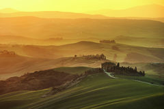 Toskana-Frühling, Rolling Hills auf nebelhaftem Sonnenuntergang Landwirtschaftliche Landschaft Lizenzfreies Stockfoto