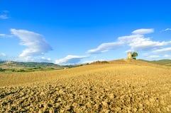Toskana, Maremma Landschaft. Ländlicher Kontrollturm, gepflogenes Feld, Dorf auf Hintergrund. Stockbild