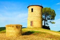 Toskana, Maremma-Sonnenunterganglandschaft. Ländlicher Turm und Baum auf Hügel. Stockbild