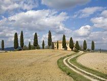 Toskanische Landschaft, Bauernhof und Zypresse Lizenzfreies Stockbild