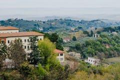 Toskanische Landschaft mit Bäumen, Häusern und grünen Hügeln in Toskana, Italien Lizenzfreies Stockbild