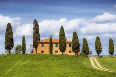 Toskanische Landschaft mit Bauernhaus- und Zypressenbäumen Stockbilder