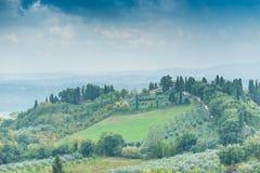 Toskanischer Landschaftsfrühherbst mit Häusern und drastischem Himmel Stockbild