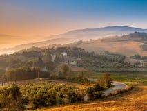 Toskanisches Dorf während des nebeligen Sonnenaufgangs Stockfotos
