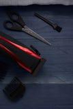 A tosquiadeira de cabelo e scissor o salão de beleza do cabeleireiro em um tabl de madeira imagens de stock