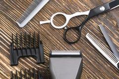 A tosquiadeira do pente, das tesouras, da lâmina e de cabelo encontra-se em uma tabela de madeira marrom Imagens de Stock Royalty Free