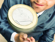 Toss a coin. Smiling businessman tossing a coin stock image