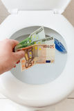 Toss Euro money in toilet bowl