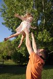 Toss Girl. Young caucasian father throwing little girl up in the air playfully at the park Royalty Free Stock Images