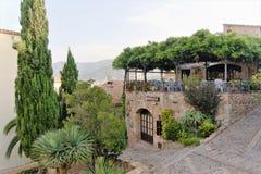 Tossa de Mar, Καταλωνία, Ισπανία, τον Αύγουστο του 2018 Ένα μικρό εστιατόριο στο παλαιό φρούριο με τα περιβάλλοντα δέντρα στοκ φωτογραφία με δικαίωμα ελεύθερης χρήσης