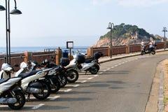 Tossa de Mar, Catalonia, Espanha, em agosto de 2018 Estacionamento da motocicleta na margem, na estrada e na vista da fortaleza imagem de stock royalty free