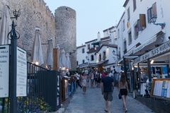Tossa de Mar, Catalonia, Espanha, em agosto de 2018 Nivelando a caminhada ao longo da parede da fortaleza entre restaurantes nume fotos de stock royalty free