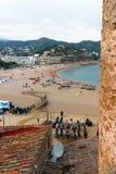 Tossa de Mar, Catalonia, Espanha, em agosto de 2018 Praia, mar, turistas e montanhas distantes no por do sol, a vista da parede d fotos de stock