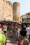 Tossa de Mar, Catalonia, Espanha, em agosto de 2018 Rua da compra perto das paredes da fortaleza velha e dos turistas de passeio imagem de stock