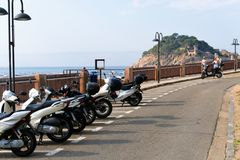 Tossa de Mar, Catalonia, Spain, August 2018. Motorcycle parking on the waterfront, the road and the view of the fortress. royalty free stock image