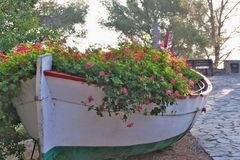 Tossa de Mar, Catalonia, Spain, August 2018. Unusual flower bed in the form of an old fishing boat in the city park. royalty free stock photo