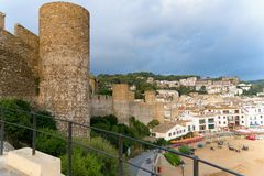 Tossa de Mar, Spain, August 2018. The fortress, the city and the beach before the summer thunderstorm. The tower and walls of the medieval fortress against the royalty free stock image