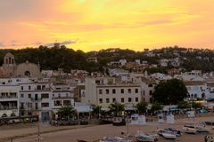 Tossa de Mar, Spain, August 2018. Sunset over the seaside town, view from the beach. An orange-yellow bright sunset over the mountains, residential buildings royalty free stock photography