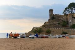 Tossa de Mar, Spain, August 2018. View of the fortress, boats on the beach and fishermen. Old Spanish fortress, winding road to it, sandy beach, boats pulled stock photos