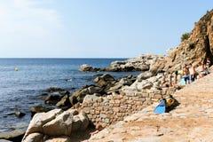 Tossa de Mar, Spanje, Augustus 2018 Steenachtig strand, vinnen voor het zwemmen van en het zonnebaden van mensen royalty-vrije stock fotografie