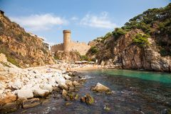Tossa de mar, view of the castle tower and city walls. Fortress on the beach side. Blue lagoon and steep cliffs. Tossa de mar, view of the castle tower and city Royalty Free Stock Image