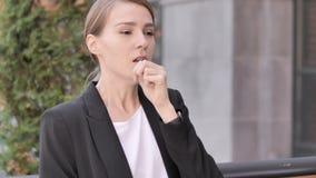 Tosse della donna di affari giovane malata Sitting Outdoor archivi video