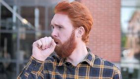 Tosse malata del giovane della barba della testarossa all'aperto video d archivio