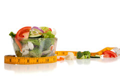 Tossed salad and tape measure on white Royalty Free Stock Image