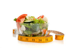 Tossed salad and tape measure on white Royalty Free Stock Photo