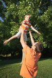 Tossing. Father tossing son in the air outdoors Royalty Free Stock Photos