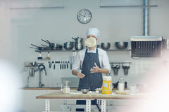 Tossing dough. Pizza chef tossing flat dough by his workplace Stock Photos