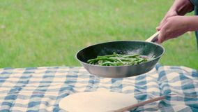 Tossing green beans in pan. stock video footage