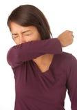 Tossir da mulher/que Sneezing no cotovelo fotografia de stock royalty free