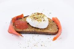 Tostada con el huevo escalfado y los salmones Imagen de archivo