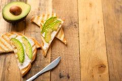 Tostada con el queso de Philadelphia, los pedazos del aguacate y las semillas de s?samo en la comida de madera del fondo, sana y  fotos de archivo libres de regalías