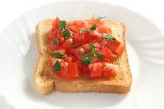 Tostada con el tomate cortado Imágenes de archivo libres de regalías