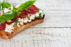 Tostada con los tomates y el queso suave asados a la parrilla Imagen de archivo