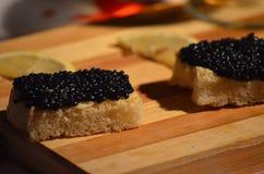 Tostada con mantequilla, el caviar y el limón Fotografía de archivo