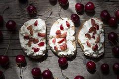 Tostada con queso y cerezas Fotos de archivo