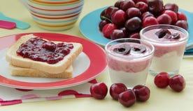 Tostada con sabor a fruta del desayuno con el atasco de cereza, el yogur de la cereza y las cerezas frescas Vajilla colorido Imagenes de archivo