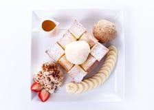 Tostada de la miel con helado de la vainilla y nata montada, miel, rebanadas de la fresa y del plátano Imagen de archivo