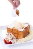 Tostada de la miel con helado de la vainilla y nata montada, miel, rebanadas de la fresa y del plátano Fotos de archivo libres de regalías