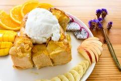 Tostada de la miel con helado y frutas de coco en una tabla de madera imagenes de archivo