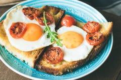 Tostada del desayuno con el huevo, los tomates asados y la ensalada del arugula Imágenes de archivo libres de regalías