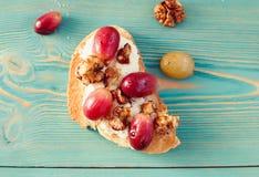Tostada dulce con la uva roja, ricotta, nuez en la tabla azul Imagen de archivo