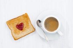 Tostada en forma del corazón con el atasco de la fruta y la taza de café Foto de archivo