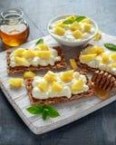 Tostada hecha en casa del biscote curruscante con requesón, la piña y la miel en el tablero de madera blanco Imagenes de archivo