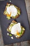 Tostada rota del aguacate y del queso Feta con los huevos escalfados Fotografía de archivo libre de regalías