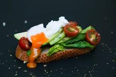 Tostada sana con el aguacate, los tomates, la espinaca y el huevo escalfado Fotografía de archivo